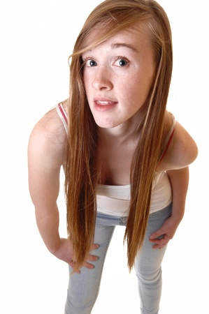 A lovely young teen girl standing and bending forward to the camera whither long brunette hair, in t-shirt and jeans for white background. photo