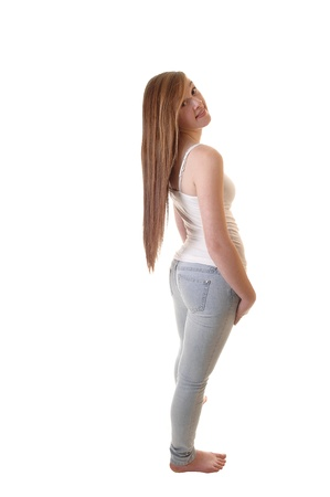 A young pretty teenager in jeans and white t-shirt standing bare feetinto the studio and her long brunette hair hanging down on her back. photo