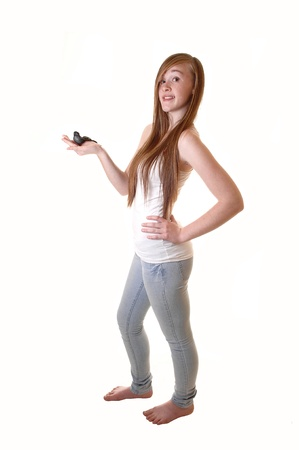 Lovely teen girl holding a black birth, in jeans and t-shirt standing bare feetin the studio with her long brunette hair, for white background. photo