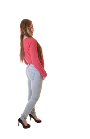 A young teenager in jeans and a red sweater and high heels standing inthe studio, with her long brunette hair, for white background. Stock Photo