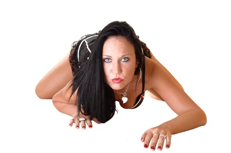 A pretty woman in a black corset crawling on the floor toward the camerawith her long black hair for white background. photo
