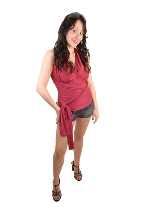 A young pretty woman in a red top and jeans shorts with long curlyblack hair standing for white background in the studio. photo