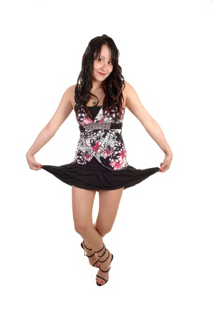 A young woman in a blouse and a short black skirt and with long curly blackhair is dancing in the studio for white background. photo