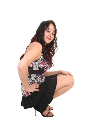 A pretty woman crouching on the floor in a short black skirt and with longcurly black hair, smiling inti the camera for whiye background. photo