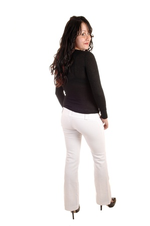 A young woman dressed up in white dress pants and a black sweaterand her long curly black hair standing from the back for white background. Imagens
