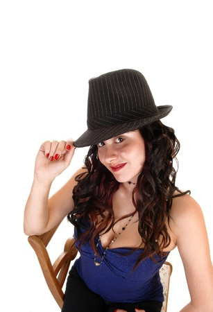 Young pretty woman with a gray hat and long black curly hair sitting ona chair, looking smiling into the camera, for white background. Stock Photo - 12076759