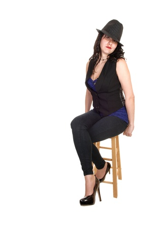 An slim gorgeous woman sitting on a chair with a black vest and blue topwith a gray hat and heels, for white background. Stock Photo - 12076751
