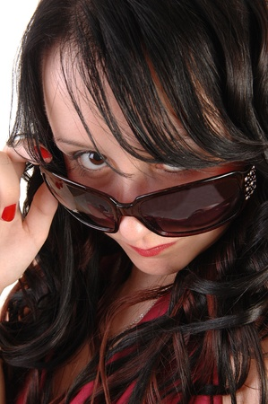 Closeup shoot of a pretty girls face with sunglasses and long black curlyhair, looking over her sunglasses. photo