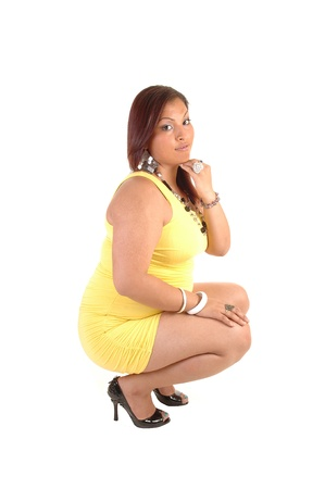 A pretty full figured young woman in a yellow dress and high heels and necklace crouching on the floor with her red hair for white background. photo