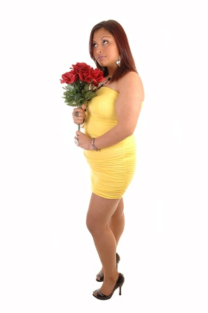 A young lovely full figured woman standing in a yellow dress, holding abunch of red roses, looking up for white background.