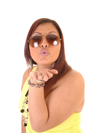 A pretty south Americanize woman with sunglasses and red hair blowinga kiss for white background, in closeup. photo