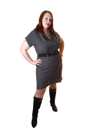A young pretty full-figured woman in a gray dress and black boots, with brown red hair standing for white background