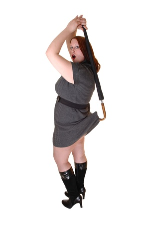 A pretty woman in a gray dress and black boots lifting with an umbrellaher dress up in the back, over white background. Foto de archivo