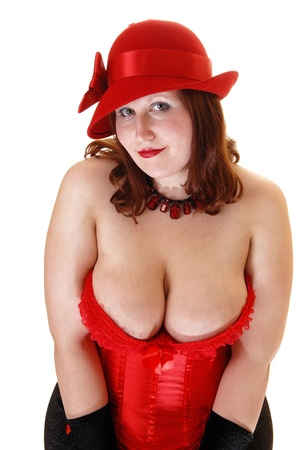 A lovely young girl in a red corset and hat, with black cloves looking intothe camera showing her big breasts, for white background.