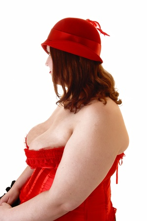 A young overweight woman in a red corset and hat sitting for whitebackground, looking away from the camera. photo