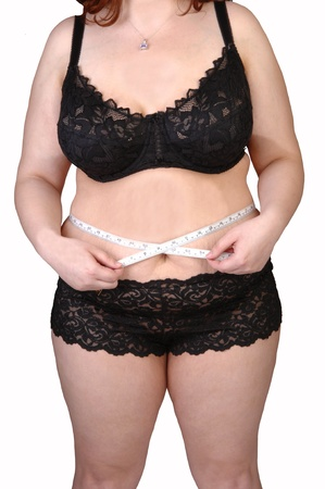 A heavy woman in black lingerie measuring her waist for whitebackground. Stock Photo