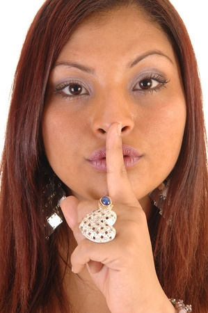 A closeup face shot of a beautiful Hispanic woman with her finger overher mouth gesturing silence. Stock Photo