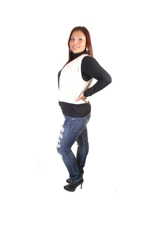 Pretty Hispanic woman in ripped jeans, a black sweater and an beigevest and boots standing in profile for white background in the studio. photo