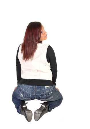 A young Hispanic woman kneeling from the back in jeans, black sweaterand beige vest with red long hair in the studio for white background. photo