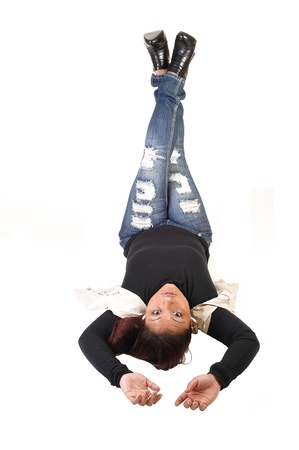 A lovely Hispanic woman lying on her back with her legs up in rippedjeans, black sweater and vest, relaxing for white background. photo