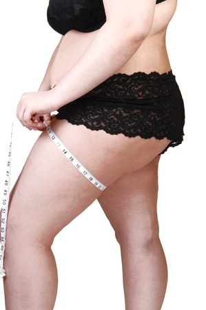 A heavy woman in black lingerie measuring her tights, showing her butt and stomach, for white background.