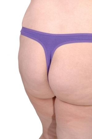 nalga: La culata de una mujer con sobrepeso en un pie tanga p�rpura en el fondo studiofor blanco.