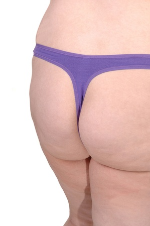 The butt of a overweight woman in a purple thong standing in the studiofor white background.