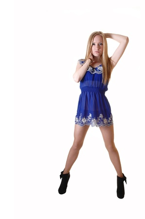 A pretty and slim young woman standing in her blue short dress and long blond long hair in black boots for white background in the studio. Stock Photo - 12330447