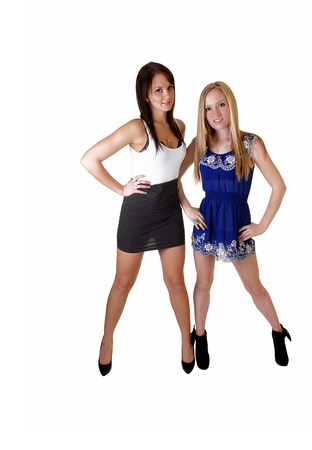 Two young a pretty woman, one in a blue dress, the other one in a graywhite dress and high heels standing in the studio for white background. photo