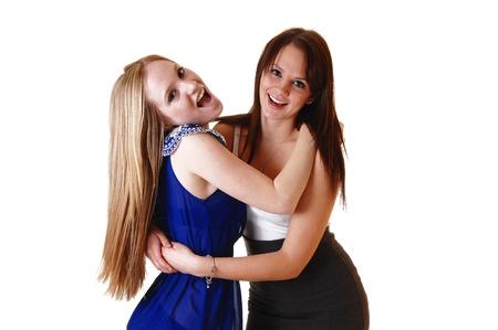 Two gorgeous young woman hugging each other and having fun in thestudio, laughing, with blond and brunette hair in a close picture. Reklamní fotografie