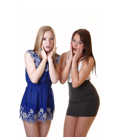Two very scared young woman standing in the studio in dresses, oneblond and one brunette, holding there faces for fiery.