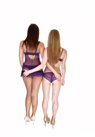 Two young pretty woman standing in lingerie in the studio from the back,showing there nice figure and bottom, in heels over white.