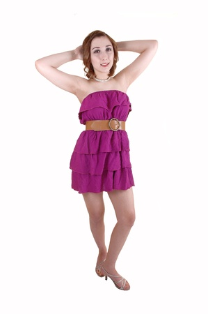 strapless dress: A pretty teenager with dark blond hair standing in a strapless dress andhigh heels in the studio, with her arms behind her head, over white  Stock Photo