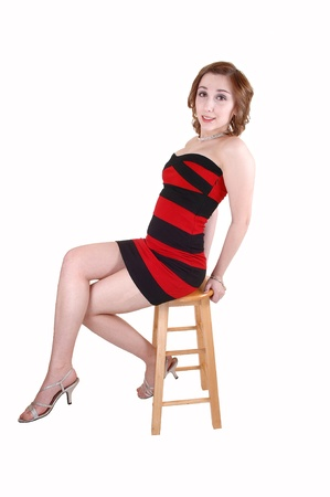 A beautiful young teenager in a red and black striped dress sitting on a chair in the studio, for white background