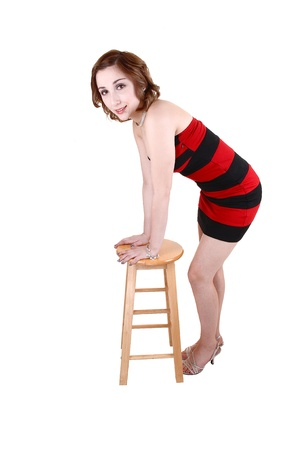 A lovely young teenager in a short red and black striped dress standingin the studio with her hands on a chair, for white background  photo