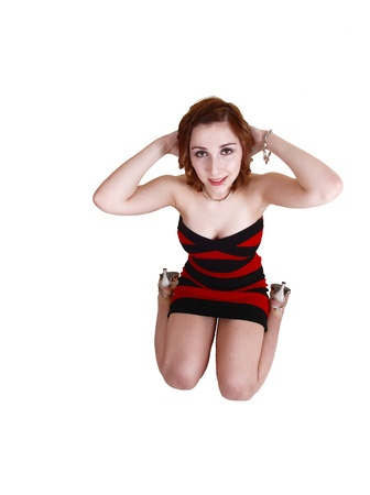 A very nice young teenager kneeling on the floor on the studio in a red andblack dress, holding her hands behind her head for white background  写真素材