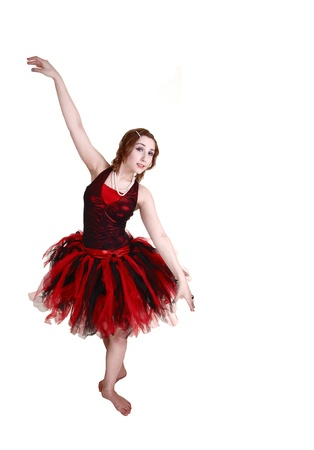 A teenage girl trying a ballet pose in her red and black outfit, bare feet,in the studio for white background  photo