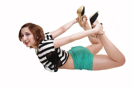An teenage girl in a black and white top and green shorts lying on herstomach doing some exercise on the floor, for white background  photo