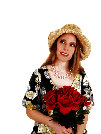 sidewards: A woman in her thirties in a dress with a straw hat and a bunch of redroses in her hand looking sidewards isolated on white background