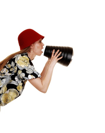 A young woman in her thirties in a dress and red hat is shouting hermessage through a cone, isolated on white background  photo