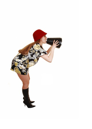 A young woman in her thirties in a dress and red hat and black boots is shouting her message through a cone, isolated on white background  photo