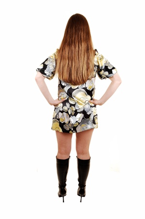 A young woman in her thirties standing from the back in a dress andblack boots showing her beautiful long blond hair, isolated on white  photo