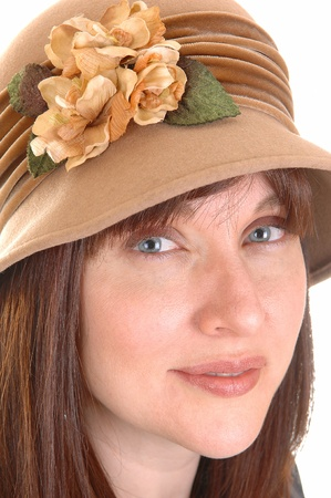 A closeup shoot of a very pretty woman in her forties with a light brownhat with beige flowers on, looking into the camera over white  photo