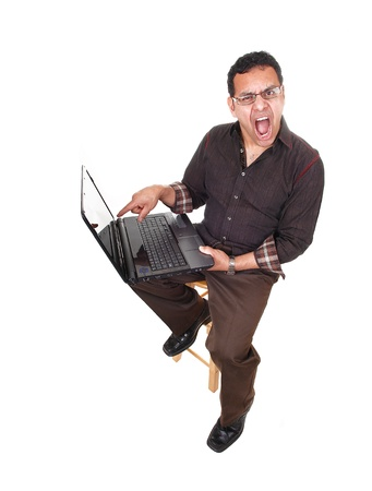 An Hispanic man with a laptop on he knees is very upset what he foundon the internet, he is shouting about, for white background