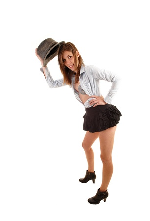 A young pretty woman in a black short skirt, boots and a gray hat, withher shirt open showing her bra, for white background in the studio  photo