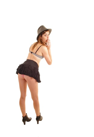 A young slim woman standing in the studio for white background fromthe back and under her short skirt showing her panties
