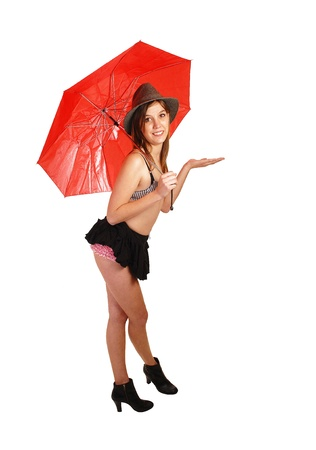 mini umbrella: A young woman with a red umbrella, black mini skirt, boots and brastanding for white background in the studio