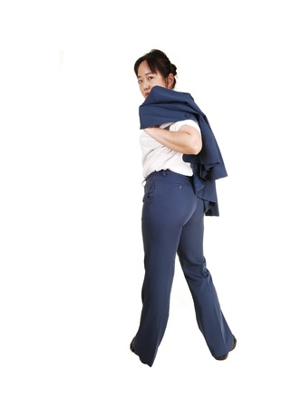 Work is finished and the Asian business woman is leaving work, withher jacket over her shoulder, from the back, looking over her shoulder Stock Photo - 13067585