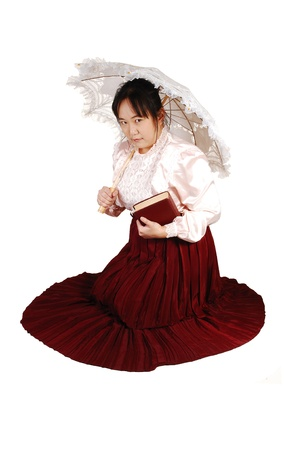 A lovely Asian Lady kneeling on the floor, holding a book and an sun-umbrella, with a long burgundy skirt over white background  photo
