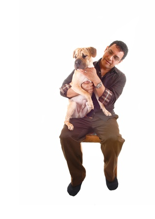 A Hispanic man in brown clothing sitting on a chair with his best friendon his lap, a sharpei puppy, for white background  Stock Photo